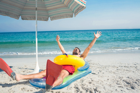 rubber ring: Man lying on the beach with flippers and rubber ring on a sunny day