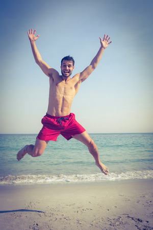 young adult: Happy man jumping on the beach on a sunny day Stock Photo