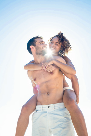 fit couple: Boyfriend doing piggy-back to his girlfriend at the beach