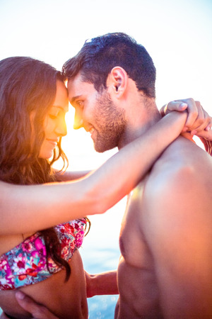 facing each other: Smiling couple facing each other on the beach on holidays Stock Photo