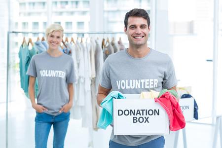 altruism: Hombre voluntario feliz celebración de una caja de donación Foto de archivo