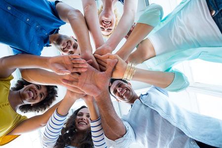 manos juntas: Equipo creativo poniendo sus manos en círculo