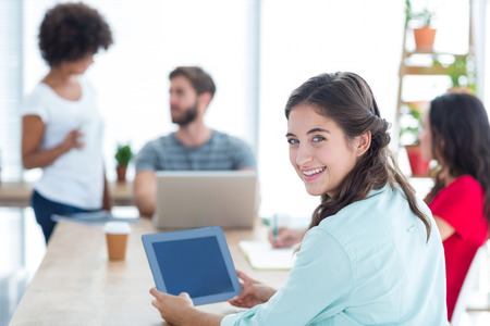 Smiling businesswoman using tablet while her team is working Imagens - 44850982