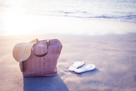 sunhat: bag with sunhat and flip flop on the sand