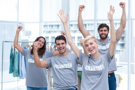 Portrait of happy volunteers friends raising arms Stock Photo