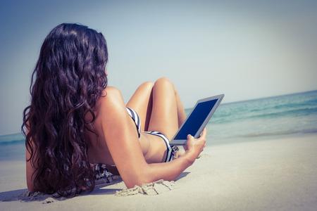capelli lunghi: Vista posteriore della bella bruna utilizzando tablet pc in spiaggia in una giornata di sole
