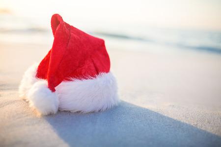 christmas time: Santa hat on the beach on a sunny day