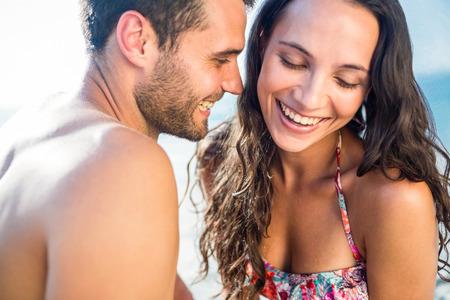 feliz pareja sonriendo a la playa