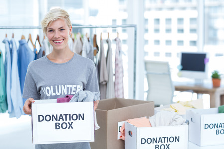 flower box: Smiling volunteer holding a box of donations in an office Stock Photo