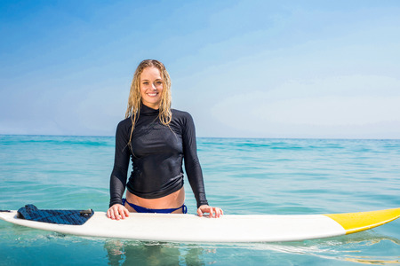 escapism: Woman with a surfboard smiling at camera on a sunny day