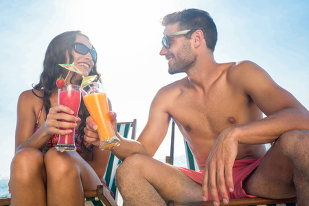 sexy couple on beach: happy couple smiling and drinking cocktail at the beach Stock Photo