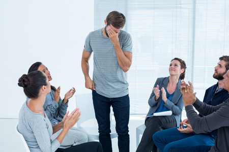 applauding: Rehab group applauding delighted man standing up at therapy session