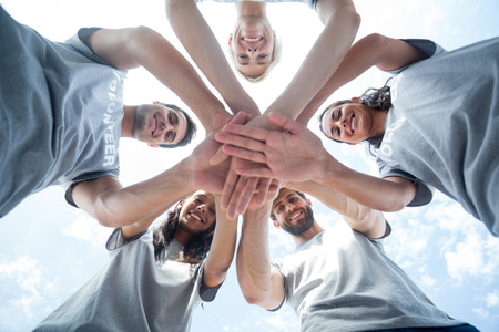 selfless: Low angle of happy volunteers putting theirs hands together Stock Photo