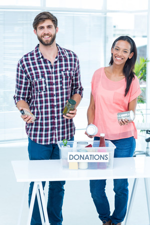 foodstuffs: Portrait of smiling young friends volunteers separating foodstuffs