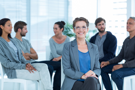 therapy group: Portrait of a smiling female therapist with group therapy in session in background Stock Photo