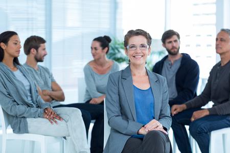 terapia de grupo: Retrato de un terapeuta de sexo femenino sonriente con la terapia de grupo en la sesi�n en el fondo