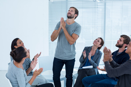 rehab: Rehab group applauding delighted man standing up at therapy session