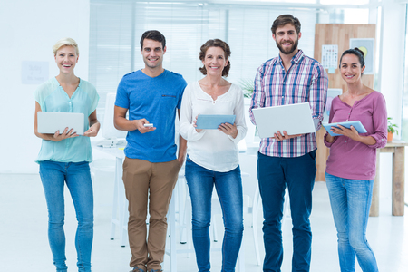 laptop stand: Young creative business people with laptop and digital tablet in the office Stock Photo