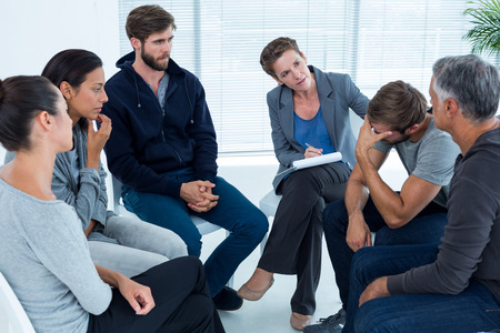 exhaustive: Concerned woman comforting another in rehab group at a therapy session Stock Photo
