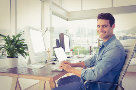 human hip: Portrait of casual young businessman using computer in office Stock Photo
