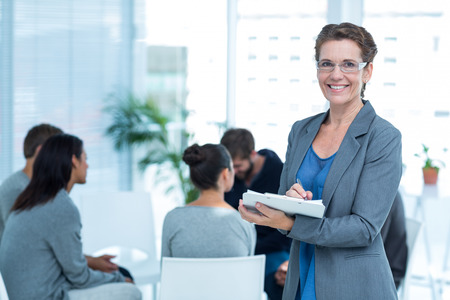 counseling: Portrait of a smiling female therapist with group therapy in session in background Stock Photo