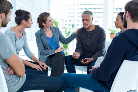 terapia grupal: Mujer en cuestión reconfortante otro en el grupo de rehabilitación en una sesión de terapia