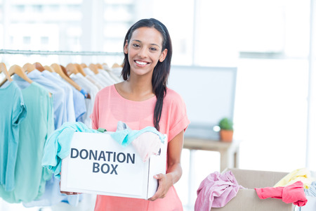 volunteer: Smiling volunteer holding a box of donations in an office Stock Photo