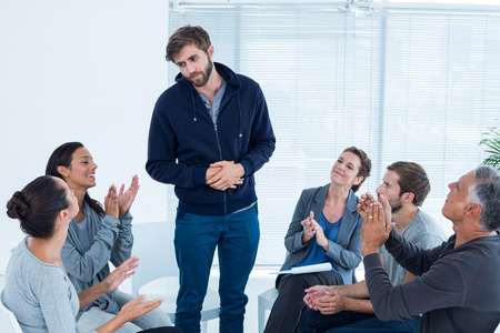therapy group: Rehab group applauding delighted man standing up at therapy session