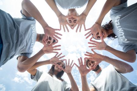 Lage hoek van gelukkige vrijwilligers spelen met hun handen Stockfoto