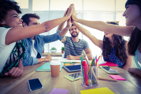 Creative business team putting hands together at the office Stock Photo