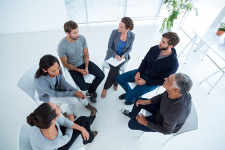 Upward angle view of a therapy group in session sitting in a circle in a bright room
