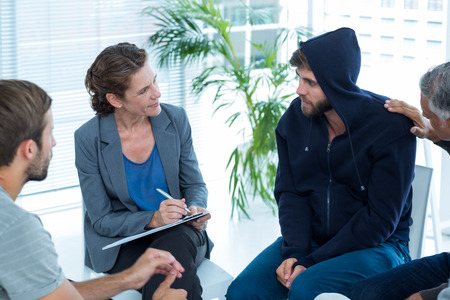 terapia grupal: Hombre Preocupado reconfortante otro en el grupo de rehabilitación en una sesión de terapia Foto de archivo