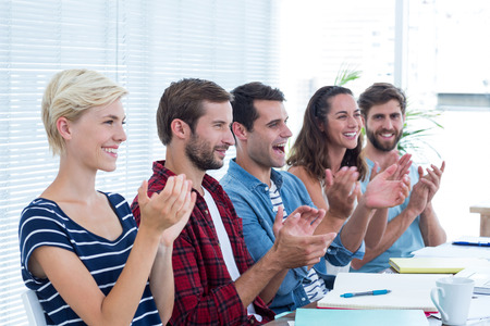 clapping hands: Young business people clapping hands in meeting at the office Stock Photo