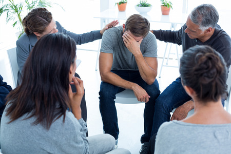 multiracial group: Concerned patients comforting another in rehab group at a therapy session