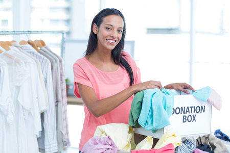 hooked up: Portrait of a smiling young female volunteer separating clothes