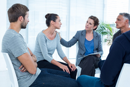 Concerned woman comforting another in rehab group at a therapy session Stock Photo