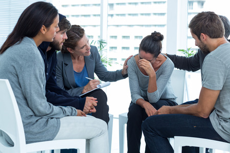 people problems: Concerned patients comforting another in rehab group at a therapy session