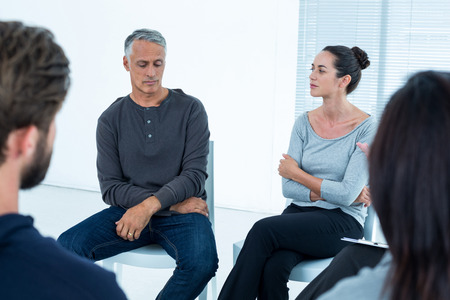 groepstherapie: Group therapy in session sitting in a circle in a bright room Stockfoto