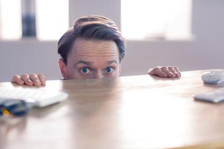 nerveux: Affaires nerveux regardant au-dessus bureau dans son bureau