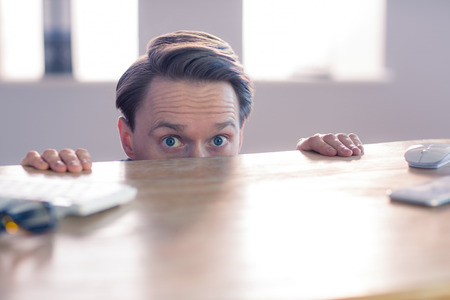 scared: Nervous businessman peeking over desk in his office Stock Photo