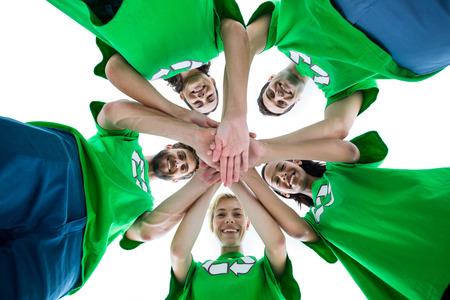 circulo de personas: retrato de ángulo bajo de los amigos que usan las camisas de reciclaje poniendo el suyo manos juntas