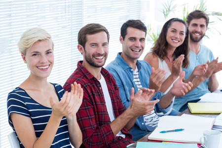 clapping hands: Young smiling business people clapping hands in meeting at the office