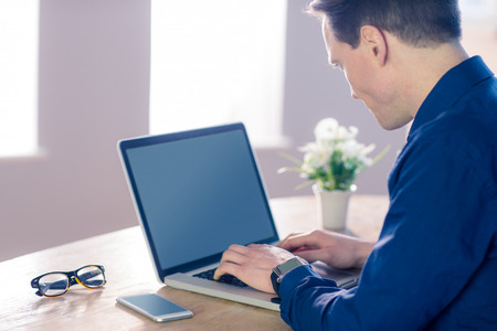 sitting in chair: Businessman typing on his laptop in his office Stock Photo