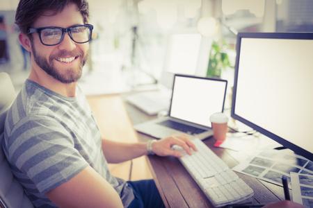 Portret van een casual jonge zakenman met behulp van de computer op kantoor