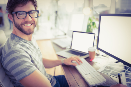 oficina: Retrato de un joven empresario ocasional usando la computadora en la oficina