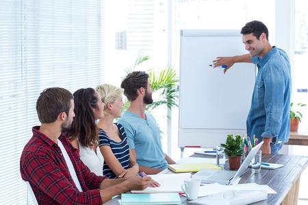 Casual affärsman ger en presentation till sina kolleger