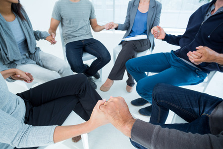 Group therapy in session sitting in a circle in a bright room Imagens