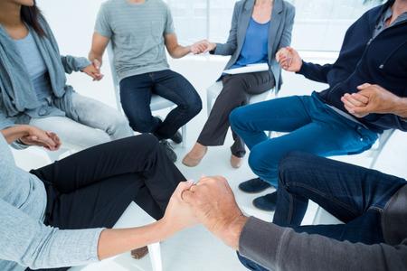 terapia grupal: La terapia de grupo en la sesión que se sienta en un círculo en una habitación luminosa
