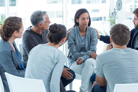 health problems: Concerned men comforting another in rehab group at a therapy session