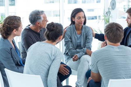 terapia grupal: Hombres Preocupados reconfortante otro en el grupo de rehabilitación en una sesión de terapia Foto de archivo